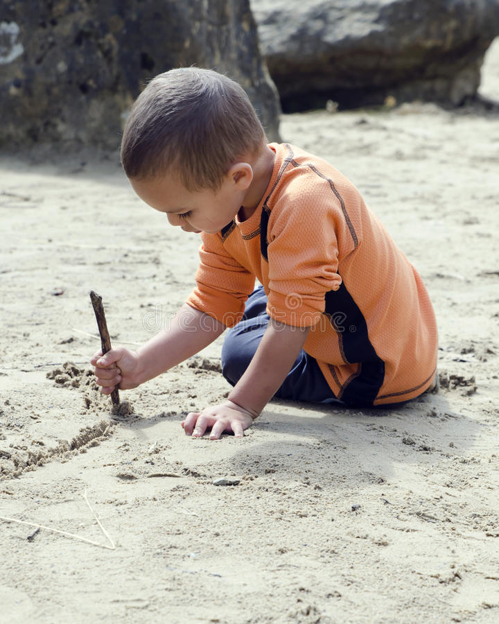 Child drawing into sand royalty free stock images