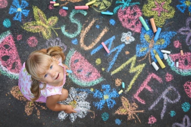 Child drawing summer spirit on asphalt stock images