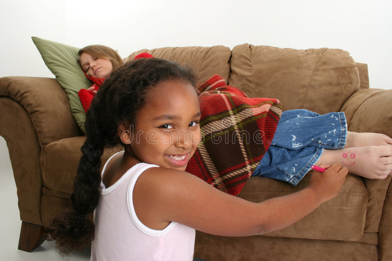 Child drawing on teenager. Smiling child drawing face on foot of sleeping teenager on sofa, white background stock photos