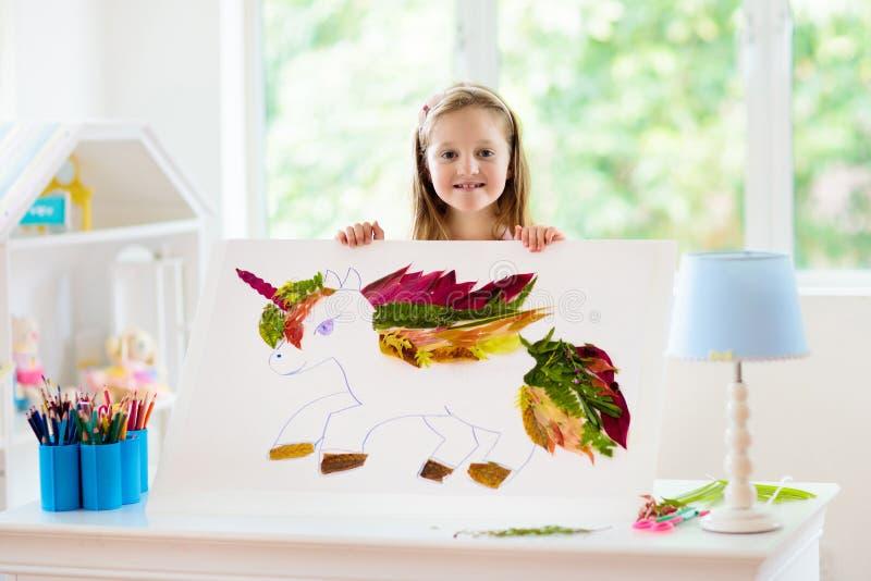 Child drawing unicorn using tree leaves royalty free stock photos