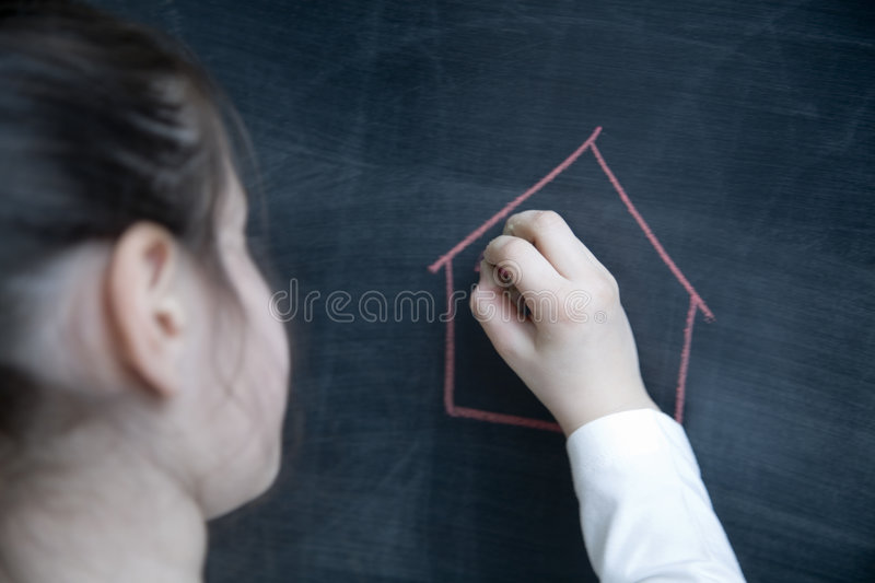 Child drawing whit a chalk. Child drawing on a blackboard with a chalk royalty free stock image
