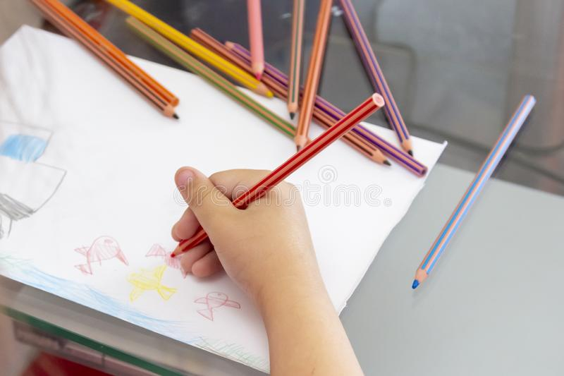 Child draws with colorful pencils. Children`s drawing on theme of fishing with goldfish, car stock photos