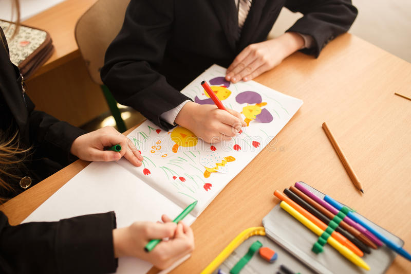 Child draws felt-tip pens. Small child holds a blue felt-tip pen in hand and draws . A kids drawing, a set of colored felt pens on stock image