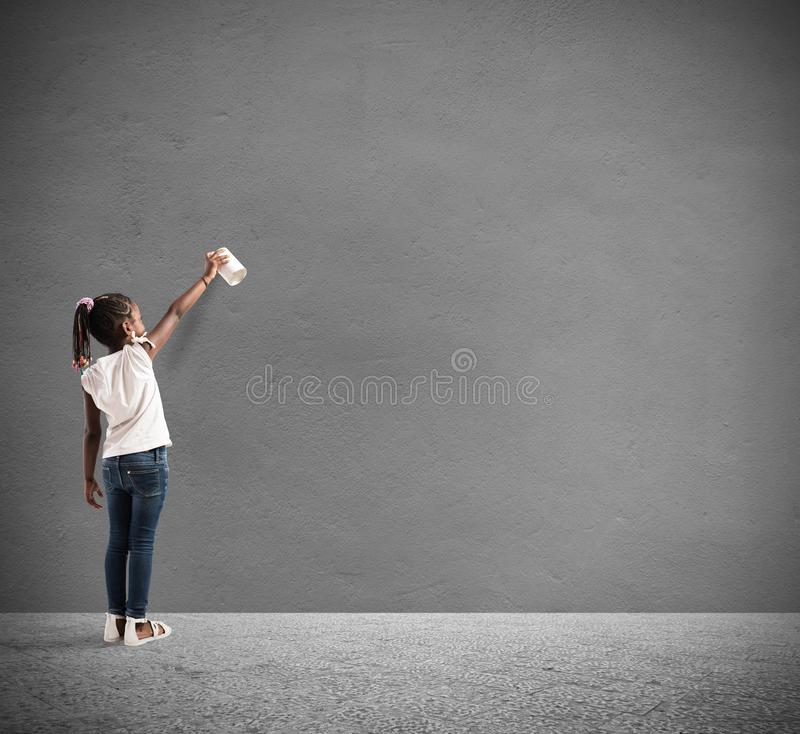Child draws with spray in a wall royalty free stock image