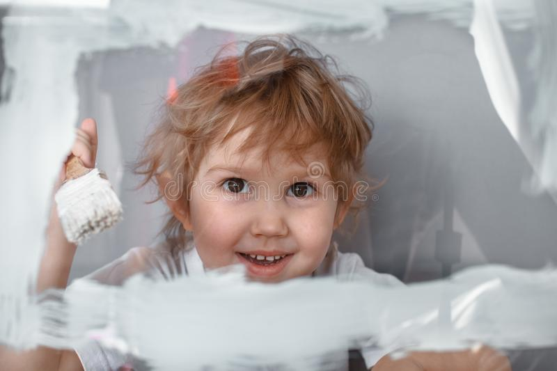 The child draws a white paint on a glass Board. Simulated screen. Happy child with brush royalty free stock photos