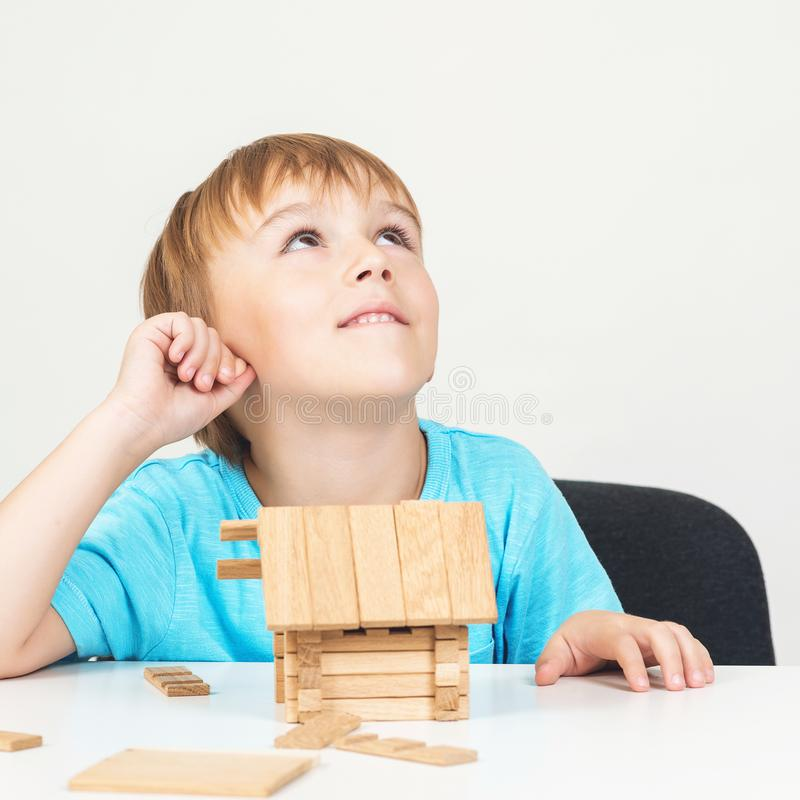 Child dreams about family home. Toy blocks house. Little boy builds small wooden house. Real estate concept. Kids dreams. Little b. Uilder create construction stock image