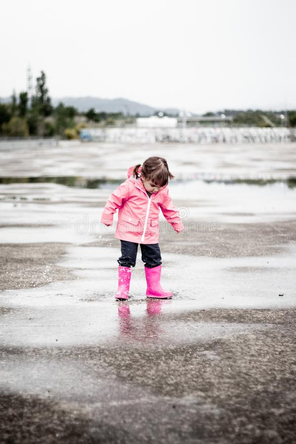 Child dressed in pink clothes jumping in puddles stock images