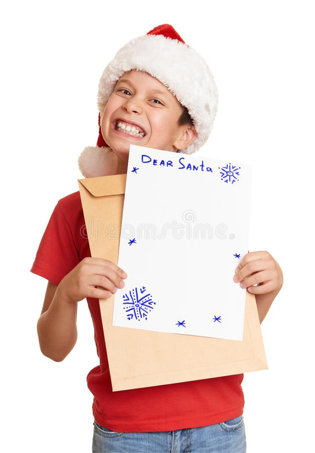 Child dressed in santa hat with letter isolated on white background. New year eve and winter holiday concept. royalty free stock photography