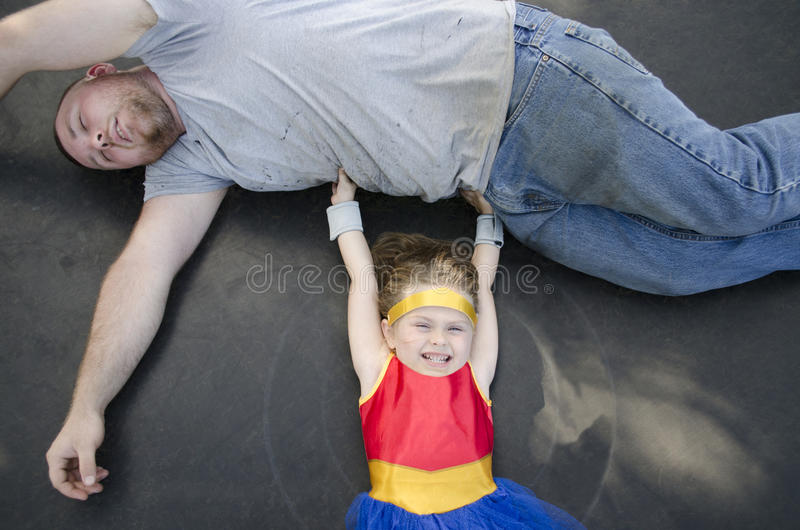 Child Dressed Up Like A Superhero Lifting Her Dad royalty free stock image
