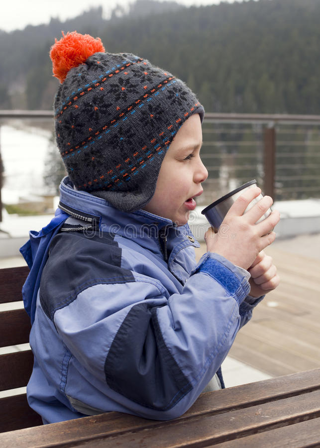 Child drinking from flask in winter stock photos