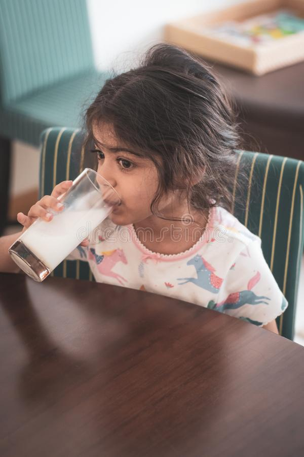 Child drinking a glass of milk at breakfast - just out of bed. stock photos