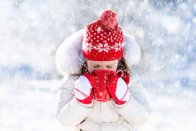 Child drinking hot chocolate in winter park. Kids in snow on Christmas. royalty free stock images