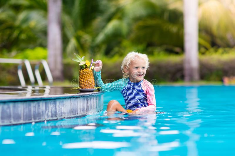 Child drinking juice in swimming pool bar. Summer family vacation with kids. Little girl holding fresh pineapple cocktail in swim up beach cafe. Kid with stock photo