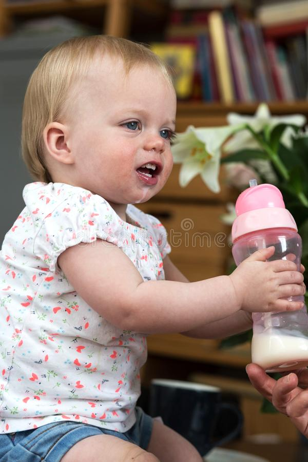 Child drinking milk from bottle, adorable and cute baby stock photos