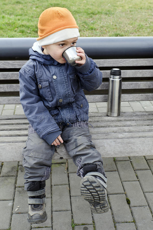 Child drinking tea from flask. royalty free stock photography
