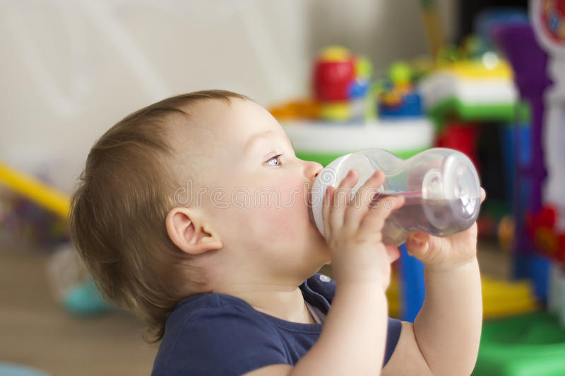 Child drinking water from a bottle stock photo