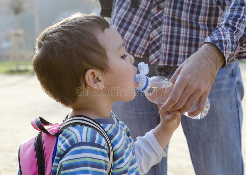 Child drinking water from a bottle. Child drinking water from a platic bottle, his father helping him stock photo