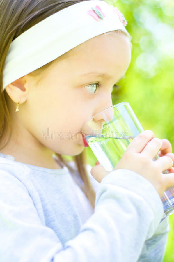 Child drinking water. Cute little girl drinking water outdoors stock photos
