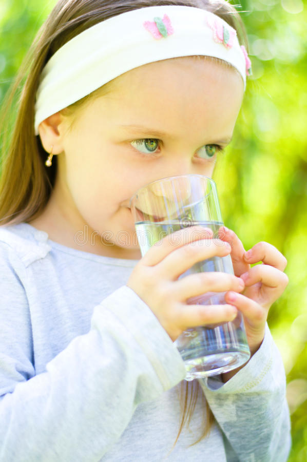 Child drinking water. Cute little girl drinking water outdoors royalty free stock images