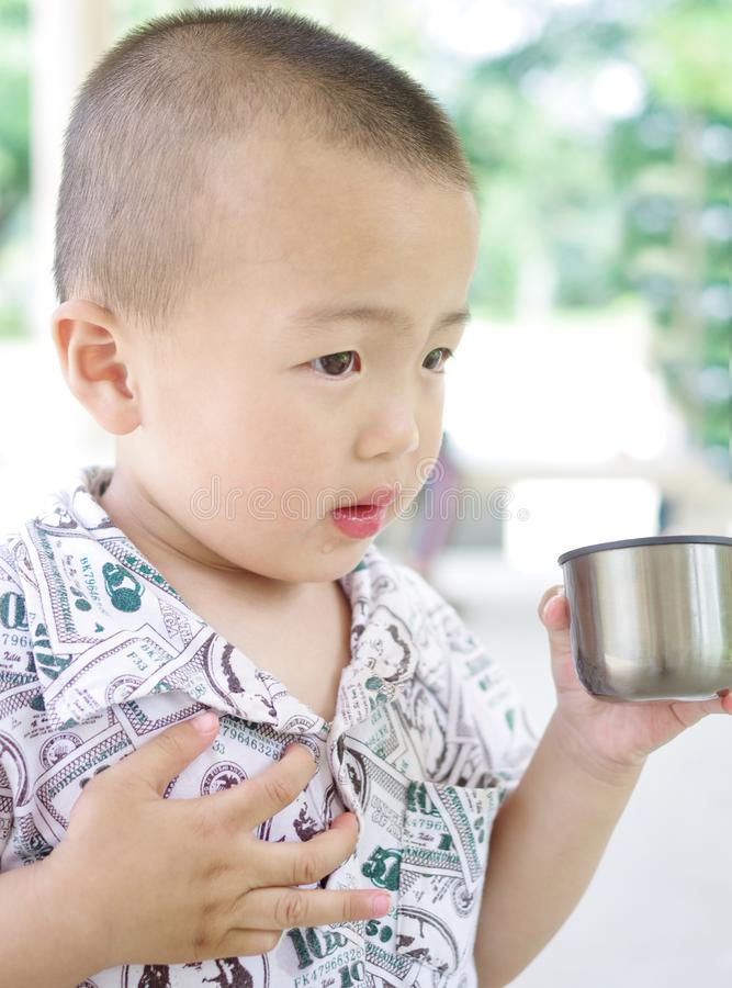 A child is drinking water. Child drink water cup summer health summer young nature royalty free stock photography