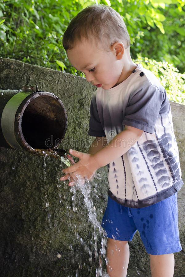 Child at drinking water pipe fountain. stock photography
