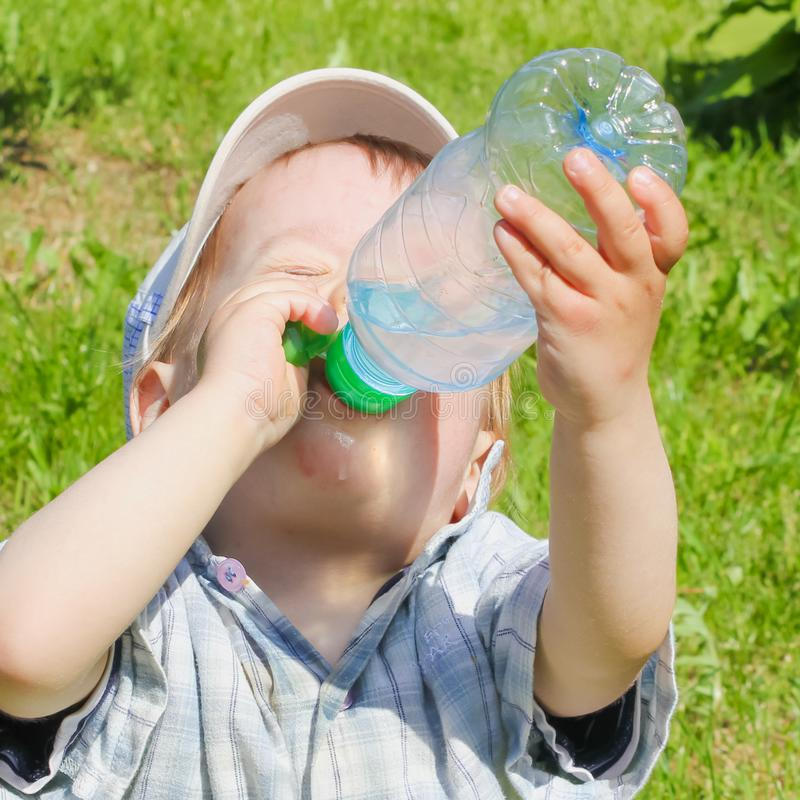 A child drinks water from a bottle. The child, the boy, quenches stock photo