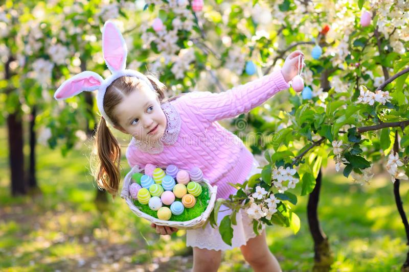 Child with bunny ears on garden Easter egg hunt. Child on Easter egg hunt in blooming cherry tree garden with spring flowers. Kid with colored eggs in basket royalty free stock photography