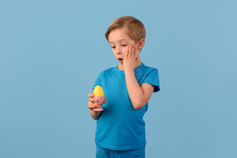 Child and Easter. Smiling blond boy, 6 years old, is holding a yellow egg in his hand. stock photography