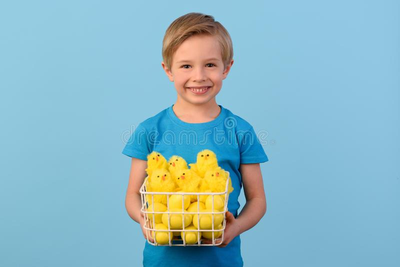 Child and Easter. Smiling blond boy, 6 years old, is holding a yellow eggs. stock photography