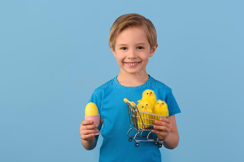 Child and Easter. Smiling blond boy, 6 years old, is holding a yellow eggs. stock photo