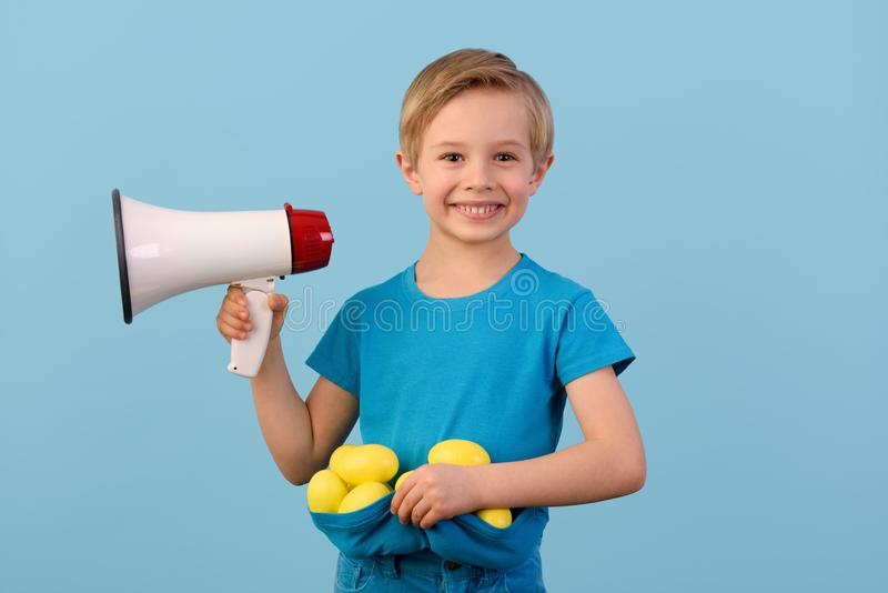 Child and Easter. Smiling blond boy, 6 years old, is holding a yellow egg and megaphone.. stock image