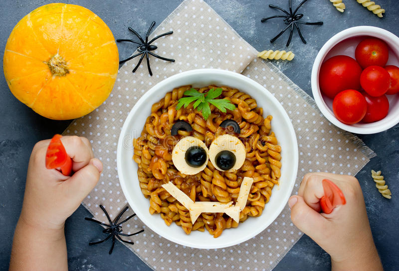 Child eat pasta with sauce in the shape of a smiling vampire face, funny dinner or lunch in Halloween style. Creative idea for sc. Hoolboy food. Fun with food stock images