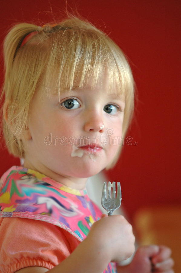 Child Eating. Little girl eating with small fork and bib stock images