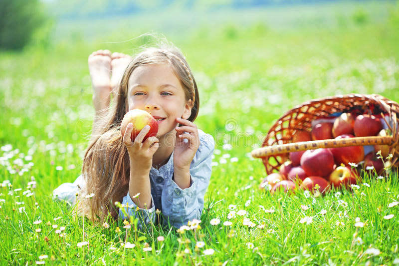 Child eating apple in a field stock photo
