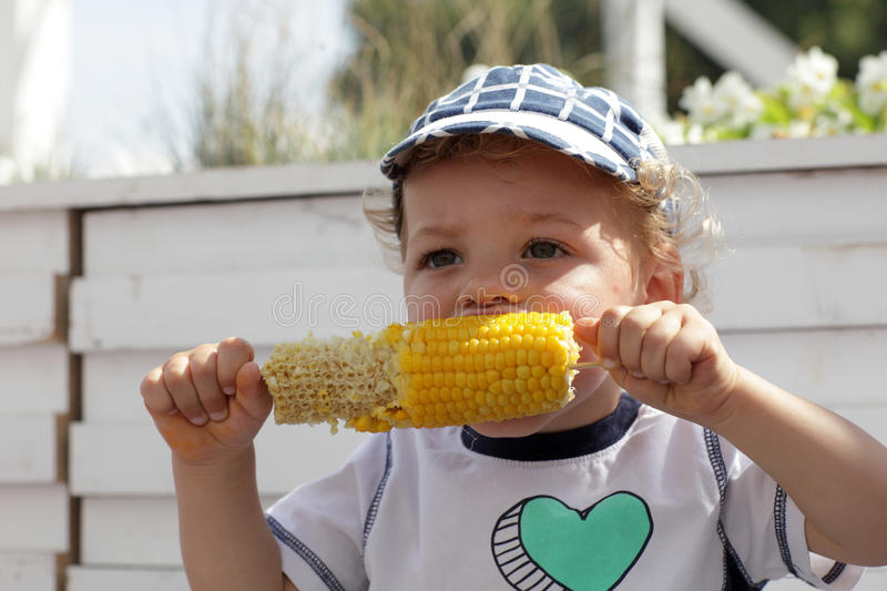 Child eating boiled corn stock photo