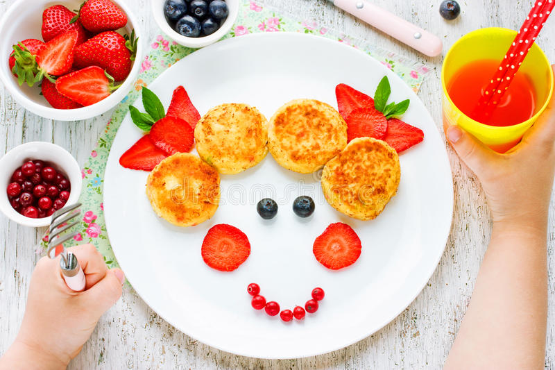 Child eating breakfast concept. Fun food for kids. Picture from. Cheesecakes with berries on plate. Girls face from edible products top view stock photos