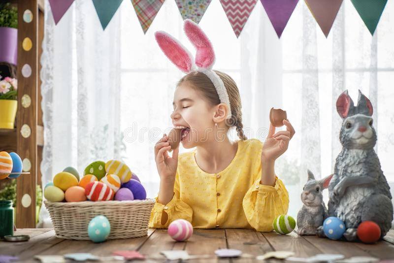 Child is eating chocolate eggs royalty free stock image