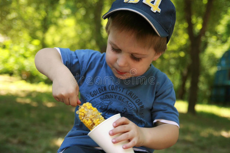 Child eating corn on the cob stock image