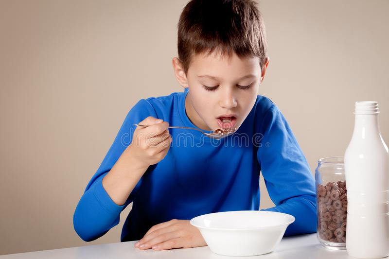 Child eating chololate cereals with milk for breakfast royalty free stock image