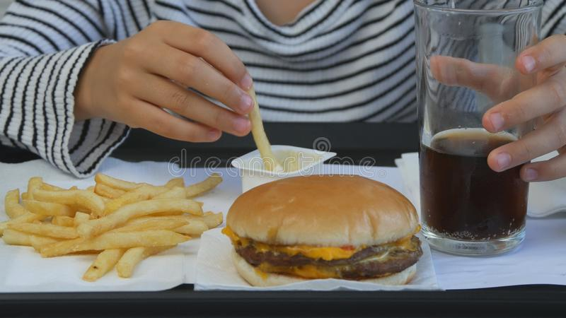 Child Eating Fast Food, Kid Eats Hamburger in Restaurant, Girl Drinking Juice stock image