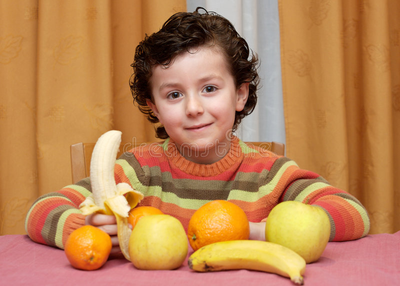 Child eating fruit. Adorable child eating fruit - focus in the face stock photos