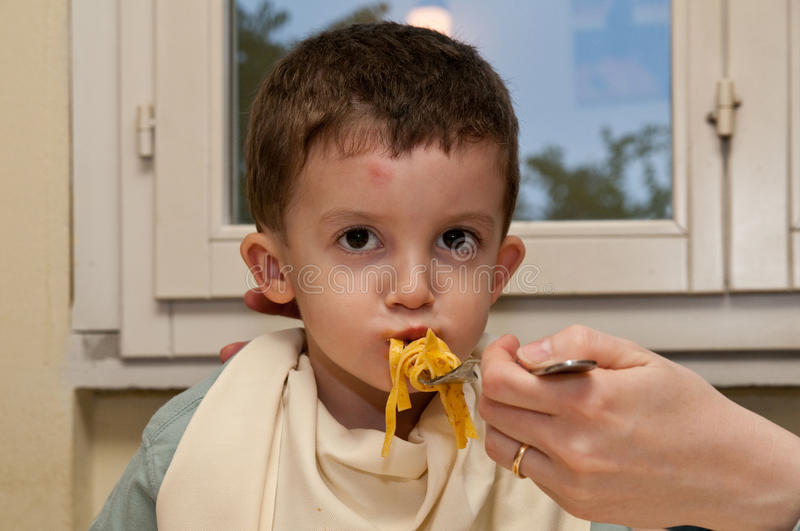 Child eating noodles. Child being embarked by the mother eats noodles stock photography