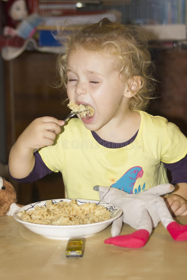 Child eating pasta royalty free stock photography