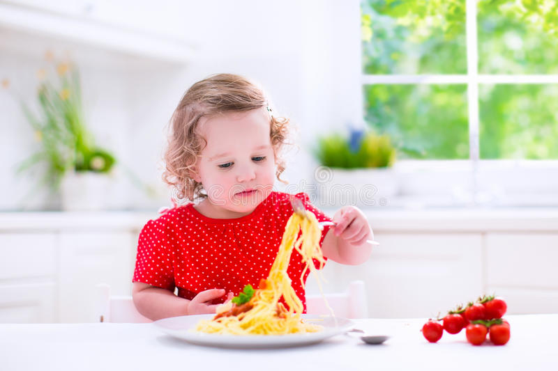 Child eating pasta. Kids eat pasta. Healthy lunch for children. Toddler kid eating spaghetti Bolognese in a white kitchen at home. Preschooler child cooking stock photos