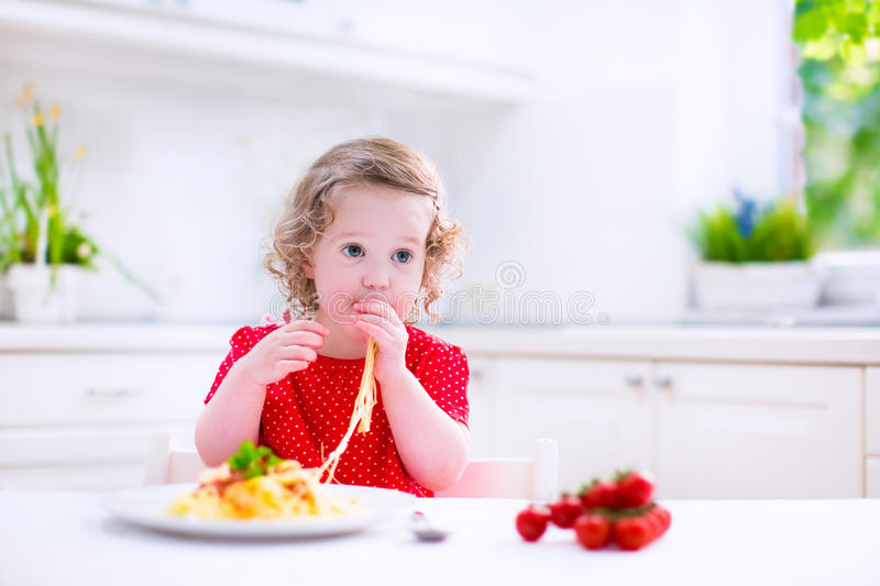Child eating pasta. Kids eat pasta. Healthy lunch for children. Toddler kid eating spaghetti Bolognese in a white kitchen at home. Preschooler child cooking royalty free stock images
