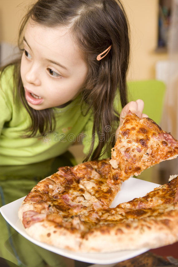 Child eating pizza. Girl eating pizza at home stock image