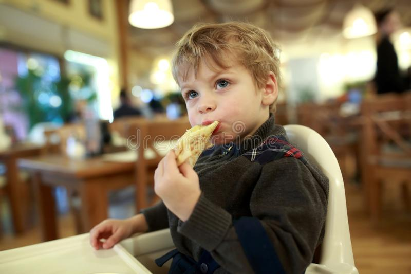 Child eating pizza stock photo