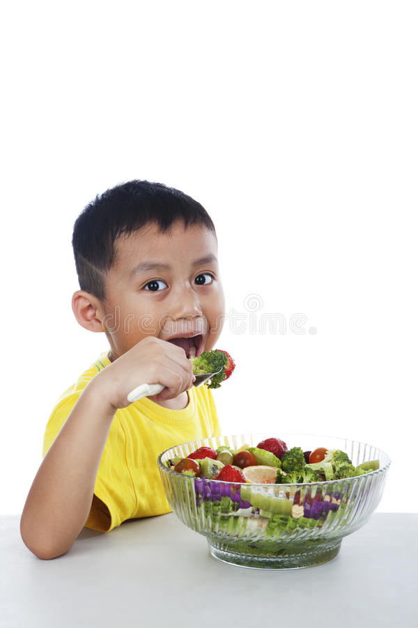 Child eating salad royalty free stock image