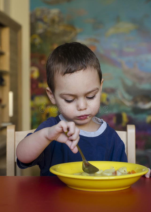 Child eating soup stock photography