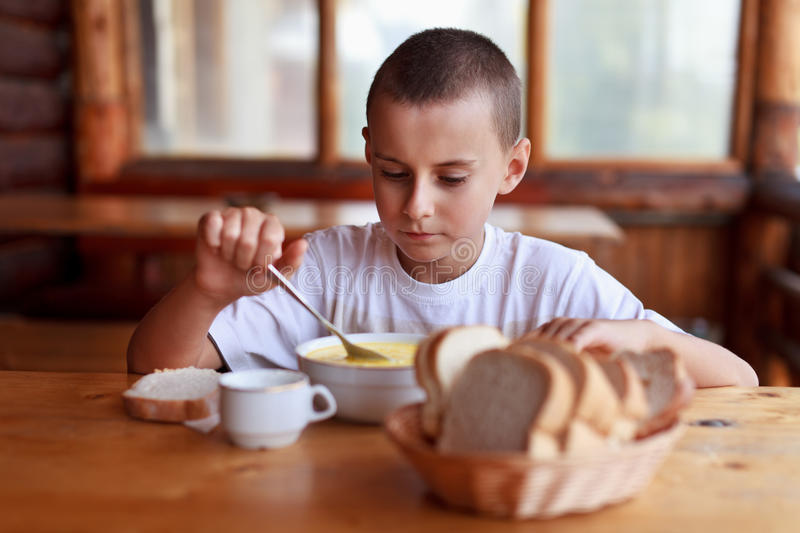 Child eating soup in a restaurant stock photos